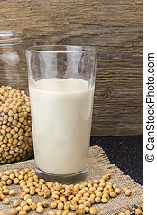 Soybeans and glass of soy milk, on wooden background.