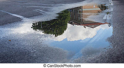 Reflection in a puddle on the pavement at home, sky, clouds