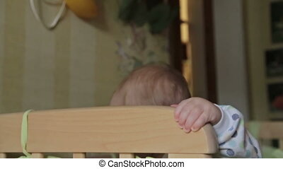 Cute baby boy standing in crib