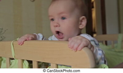 Cute baby boy standing in crib looking at camera at home,...