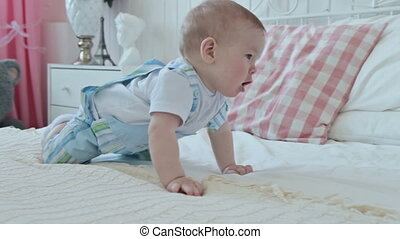 Baby crawling on the bed at home