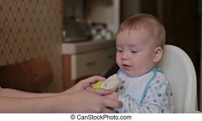 Mother gives nibbler for her son - Mother give nibbler (food...