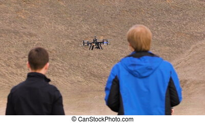 Two engineers watching the drone landing. Quadrocopters sits...