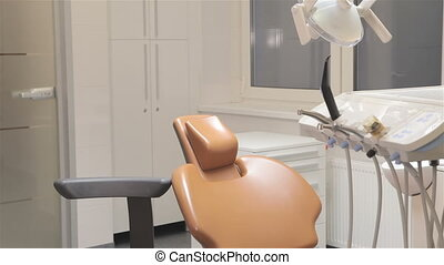 Doctor sits near dentist chair - Young dentist coming up to...