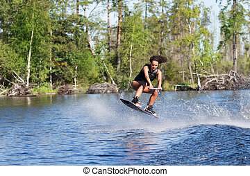 Woman study wakeboarding on a lake - Young pretty woman...