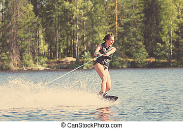 Young woman study riding wakeboarding on a lake - Young...