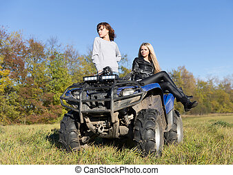 Two elegant women riding extreme quadrocycle ATV field