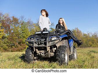 Two elegant women riding extreme quadrocycle ATV field