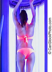 Pretty slim woman gets sun tan in solarium