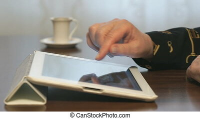 Woman's hand touches screen of a digital tablet