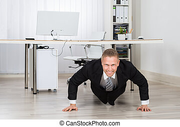 Businessman Doing Pushup At Work