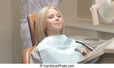 Woman receive checkup at the dentist - Male dentist...