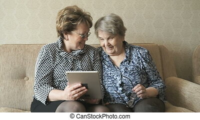 Two women watch photos using a electronic tablet - Two women...