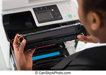 Businesswoman Fixing Cartridge In Office - Young African...