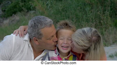 Grandparents kissing dear grandson - Grandmother and...