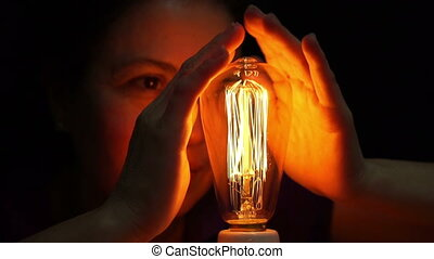 Woman Antique Filament Bulb Warming - Close up shot of a...