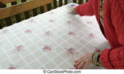 Senior woman wipes dusts dinner table on the patio - Senior...