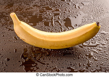 Single banana on a wet black background