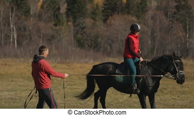 The female beginner sitting on the horseback is led in a circle by a personal trainer teaching her to keep the balance and not to fall.