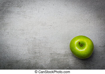 One green apple on concrete background. The apple is in the...