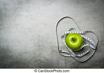 One green apple on concrete background with measure tape.