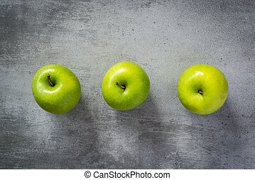 Three green apples on concrete background - Three green...
