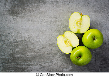 Green apples on concrete background One of the apples are...