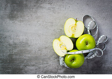 Green apples with measure tape on concrete background
