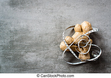 Ginger with measure tape on concrete background - Ginger...