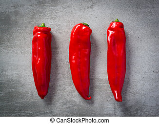 Thre red peppers on a row on concrete background