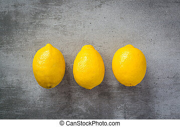 Three lemons on a row on concrete background