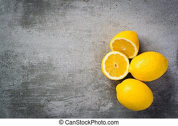 Lemons on concrete background One of the lemons are sliced