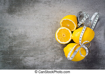Lemons with a measure tape. One of the lemons are sliced.