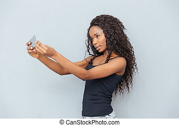 Afro american woman making selfie photo on smartphone over...
