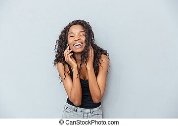 Laughing woman talking on the phone - Laughing afro american...