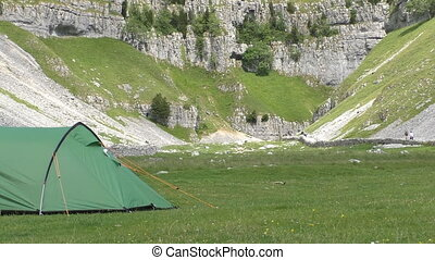 Green tent near mountains - Green tent in the foreground on...