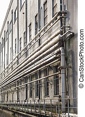 Old factory and pipes - Old pipes on the wall outside of an...