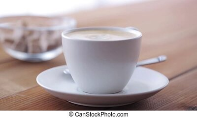 cream pouring to coffee cup on wooden table - breakfast,...