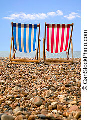 Deckchairs - Two deckchairs on a pebble beach, low...