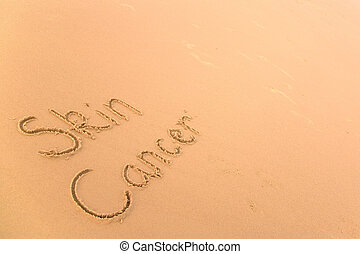 Skin cancer in sand - Skin Cancer written in sand on a...