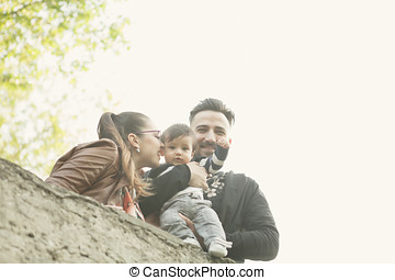 Happy family with young son walking in park