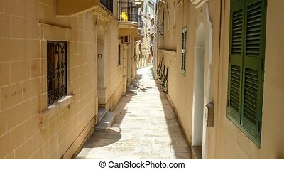 typical narrow street with stairs in the city Valetta on the...