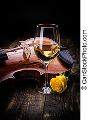 Violin, wine and yellow rose on dark wooden background