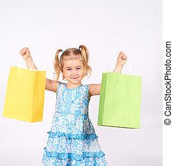 Shopping child. little girl holding shopping bags.