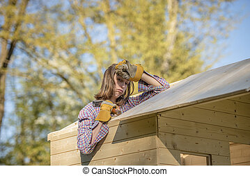 Exhuasted woman working on roof of tree house