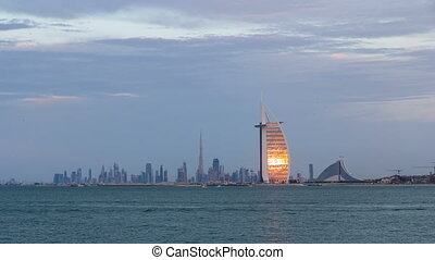 Dubai skyline with Burj Al Arab hotel during sunset and day...