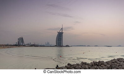 Dubai skyline with Burj Al Arab hotel during and day to night timelapse.