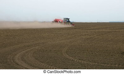 Tractor ploughs tills plows and seeds on the field - Field...