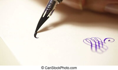 female hand writes a pen calligraphic signs close up.