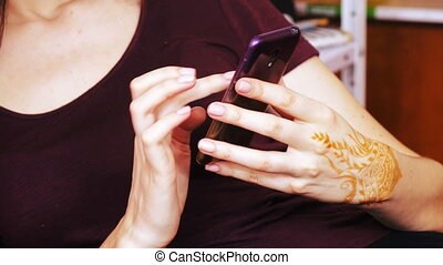 Hand with smartphone and mehendi - In hand drawing mehendi...